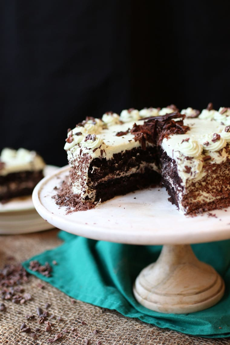 A chocolate mint cake on a cake stand with a slice cut out.