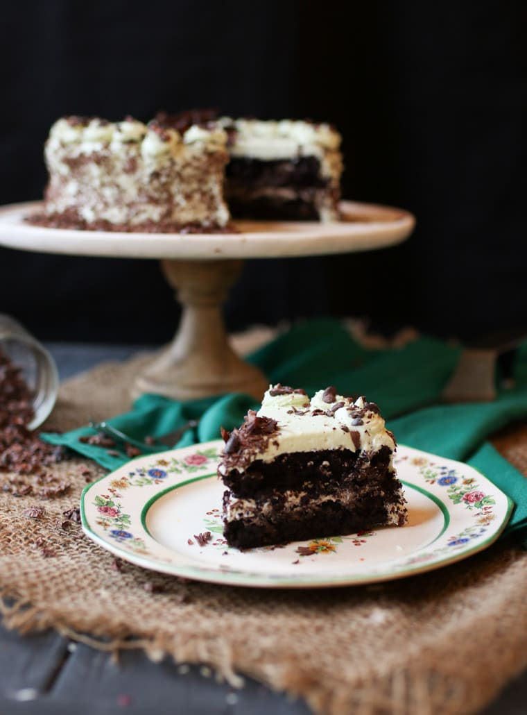 An image of a slice of chocolate mint cake with the whole cake in the background.