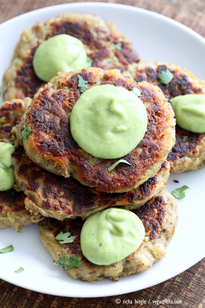 birds eye view of a stack of vegan irish potato cakes garnished with green avocado basil ranch