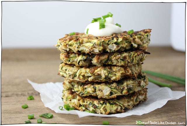 close up of a stack of vegan baked zucchini fritters for st patricks day garnished with fresh herbs