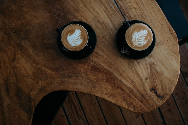 Two lattes on a wooden table.