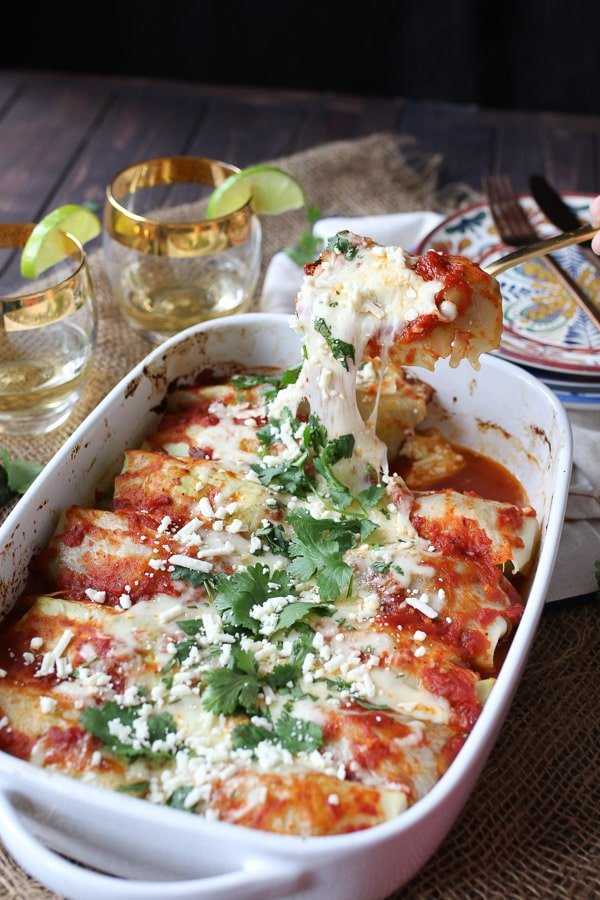 Spoon holding a serving of cheesy cabbage roll enchiladas in a white casserole dish.
