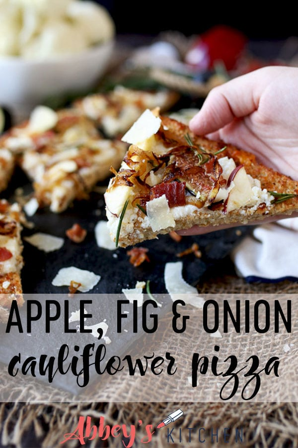 pinterest image of hand holding a slice of apple, fig and onion cauliflower pizza flatbread with text overlay