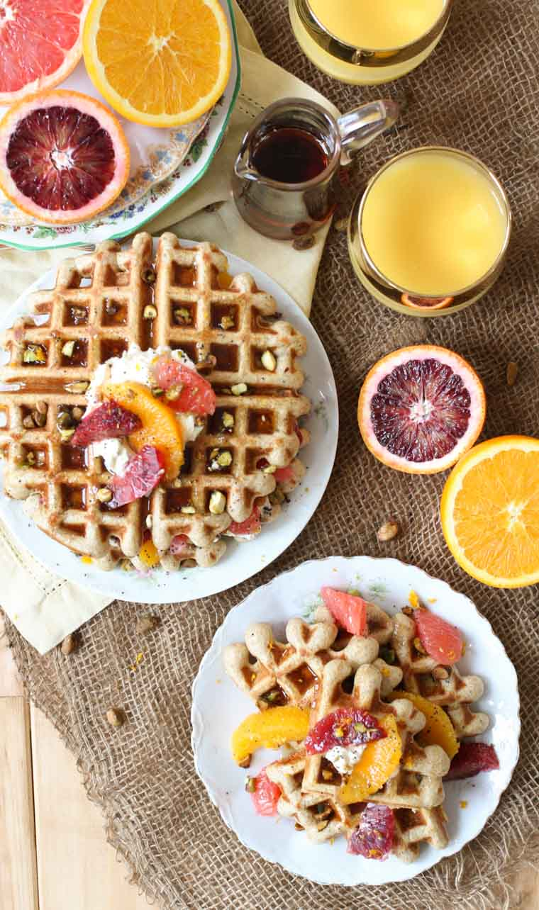 Overhead shot of a plate of vegan orange poppyseed waffles for brunch next to glasses of orange juice and maple syrup.