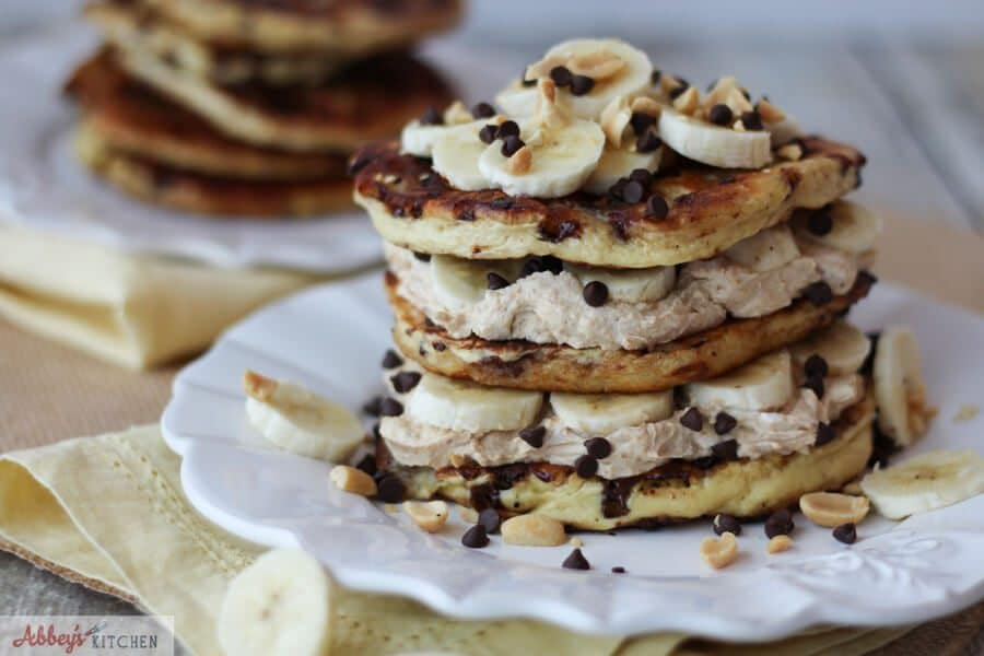 Peanut butter protein pancakes stack on a white plate topped with bananas and mini chocolate chips.