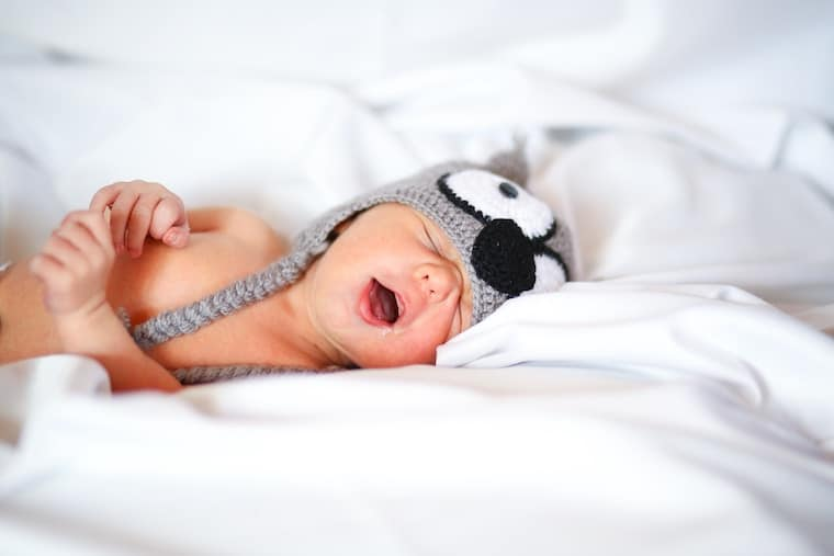 Baby lying in bed with a hat on.