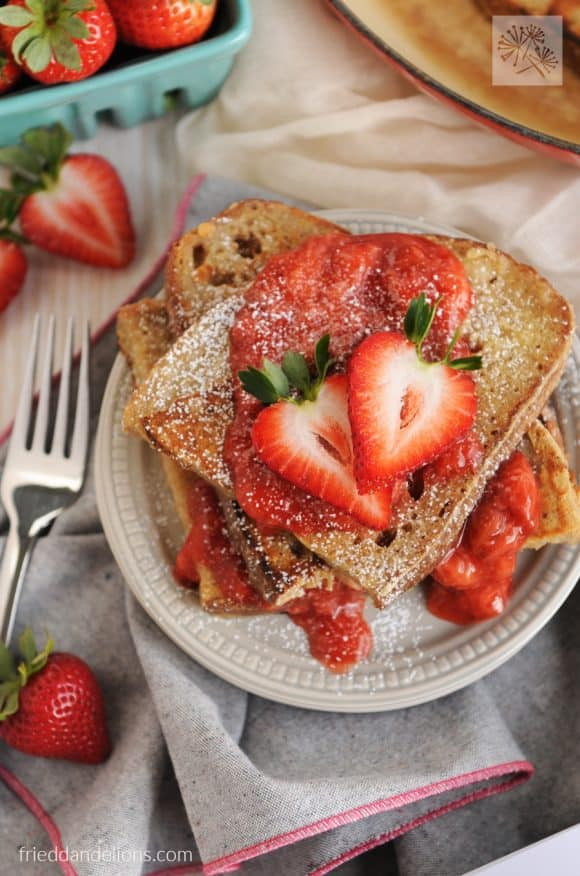 Vanilla french toast with strawberry sauce topped with fresh strawberries.