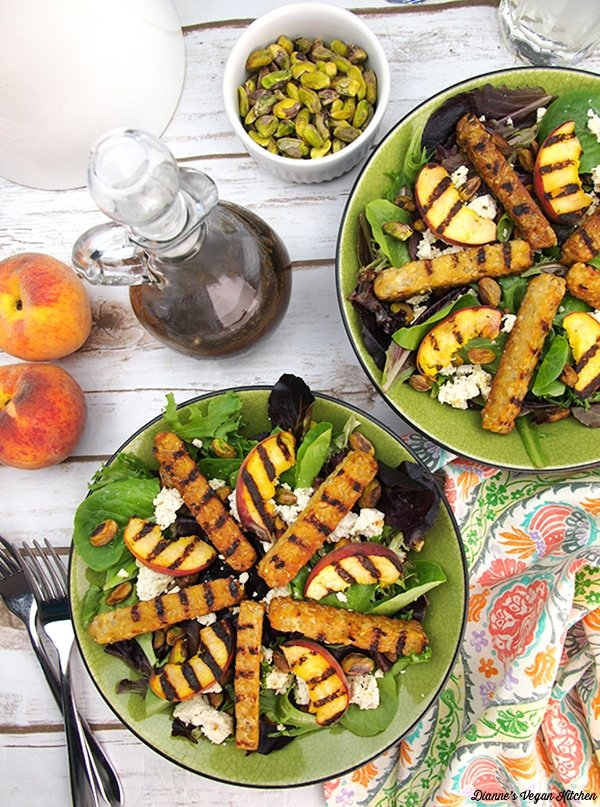 Grilled tempeh salad with peaches in a green bowl.