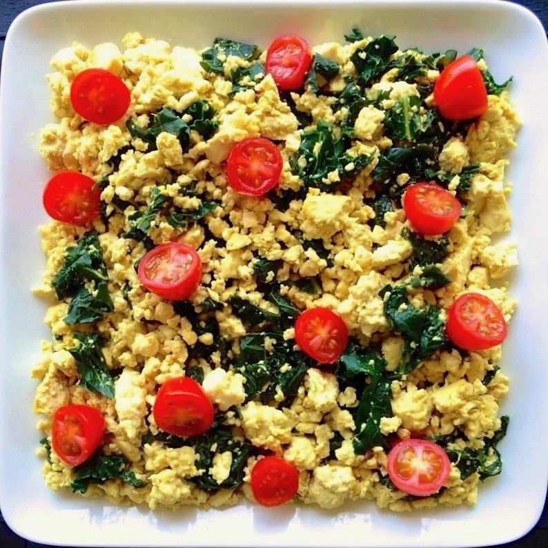 Tofu scramble with spinach and tomatoes in a white serving dish.