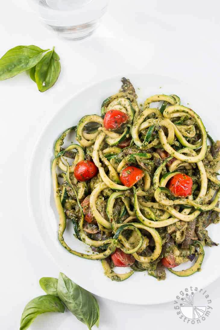 Pesto zucchini spaghetti with tomatoes on a white plate.