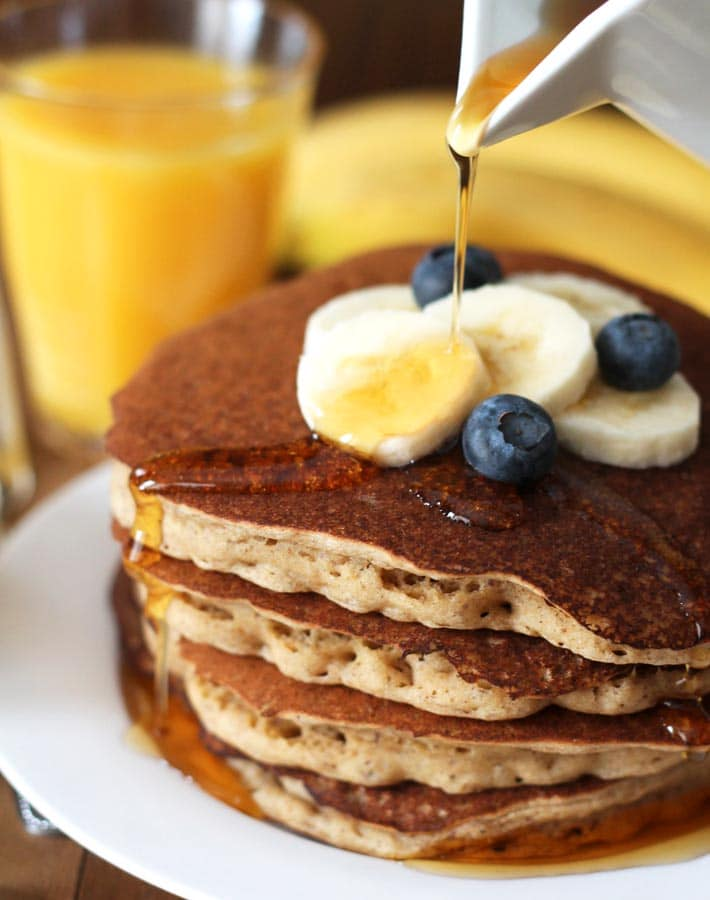 Banana pancakes topped with blueberries, sliced bananas and maple syrup.