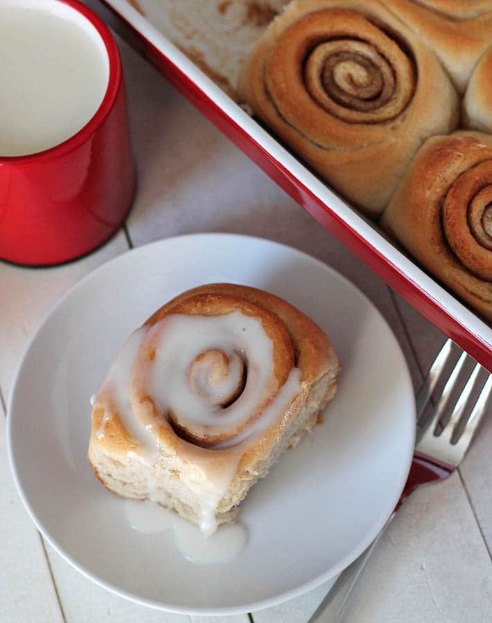 birds eye view of vegan cinnamon rolls on a white plate next to a baking dish filled with additional cinnamon rolls