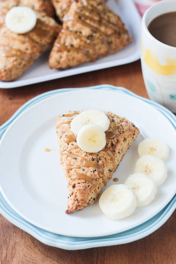 Black sesame scones topped with tahini glaze and banana slices.