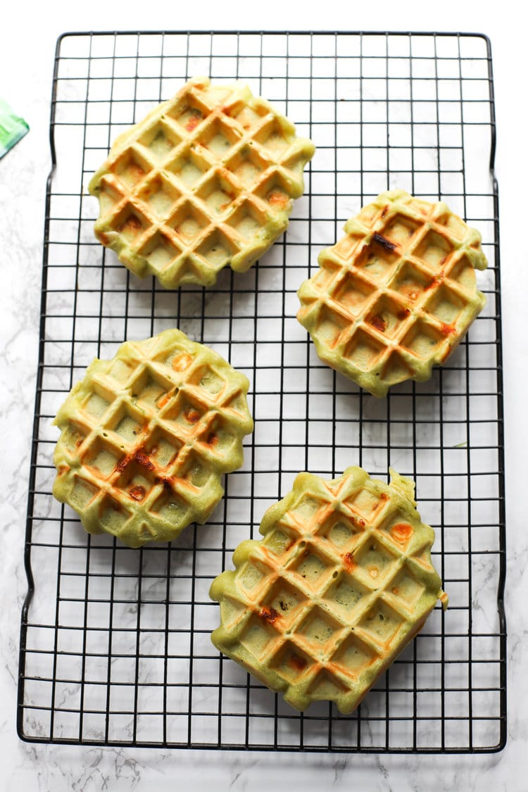 Matcha white chocolate waffles on a rack.