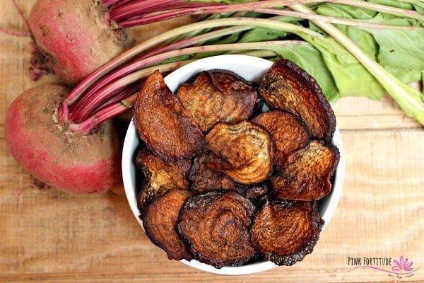 Birds eye image of vegan baked beet chips served in a large white bowl placed next to two raw beetroots, atop of a wooden surface