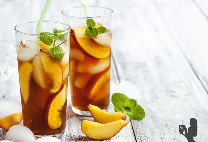 Medium close up image of two vegan peach limeade bourbon cocktails in tall clear glasses with green straws atop a wooden surface, garnished with fresh mint and additional fresh peaches