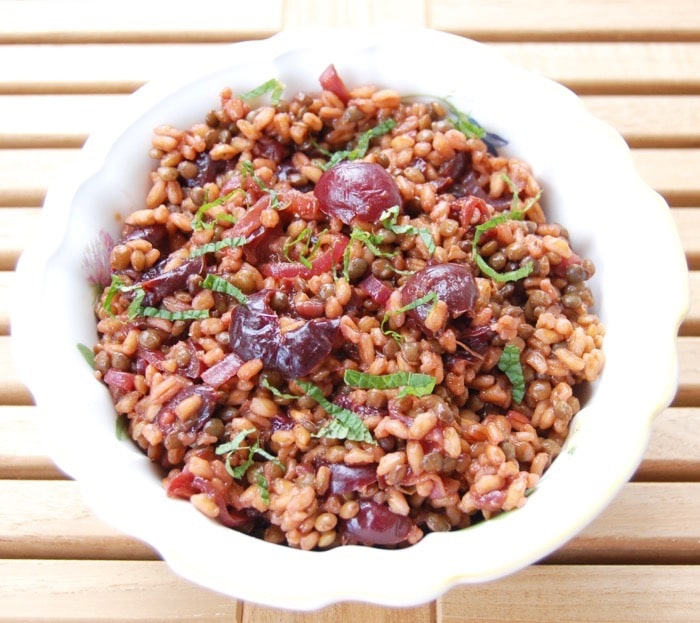 Birds eye close up image of plant-based roasted cherry and farro salad in a large white bowl, garnished with fresh herbs