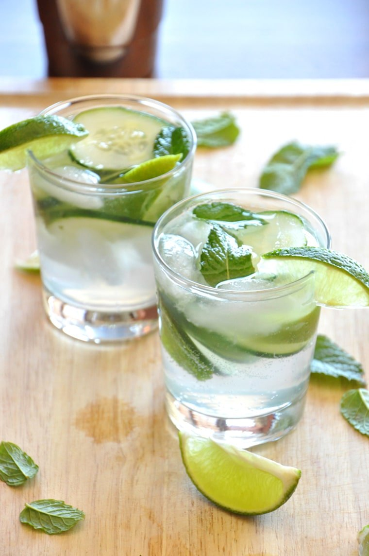 Close up image of two clear shot glasses filled with vegan cucumber cooler cocktails garnished with fresh mint and lime wedges atop a wooden surface