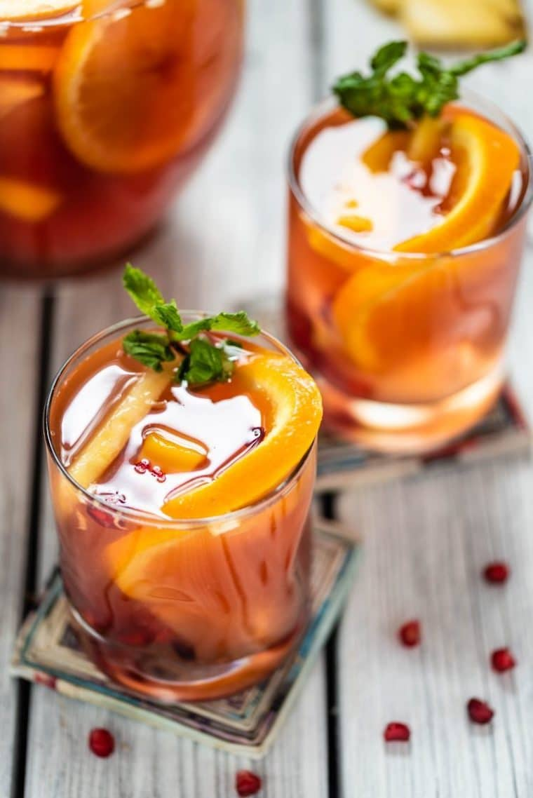 Close up image of kombucha sangria in short clear glasses on colourful square coasters, garnished with fresh mint and pomegranate seeds