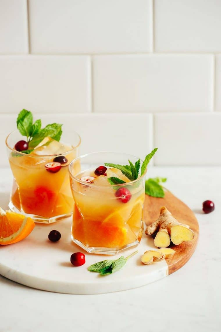 Close up of orange infused whiskey ginger in a clear glass against a white tile background, garnished with fresh cherries, mint, ginger, and orange slices