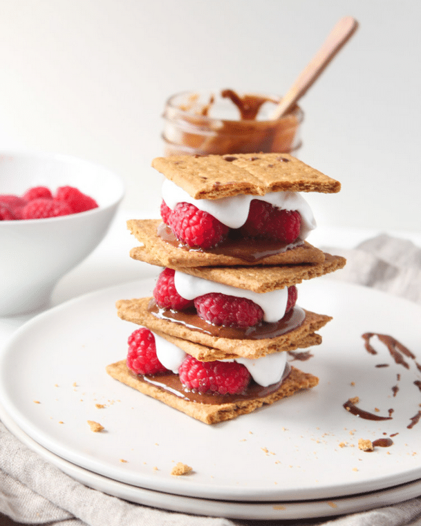 Vegan raspberry and coconut cream nutella smores stacked on top of one another on a circular white plate, garnished with additional nutella sauce, featuring a white bowl filled with raspberries and a glass jar of nutella in the background