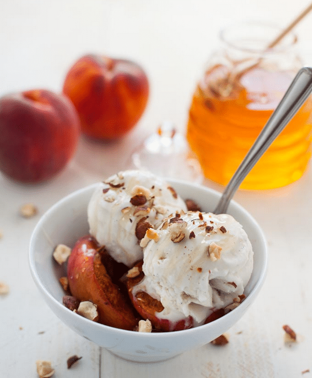 Plant-based roasted peach ice cream sunday served in a white bowl garnished with chopped nuts, and additional peaches and a jar of honey in the background