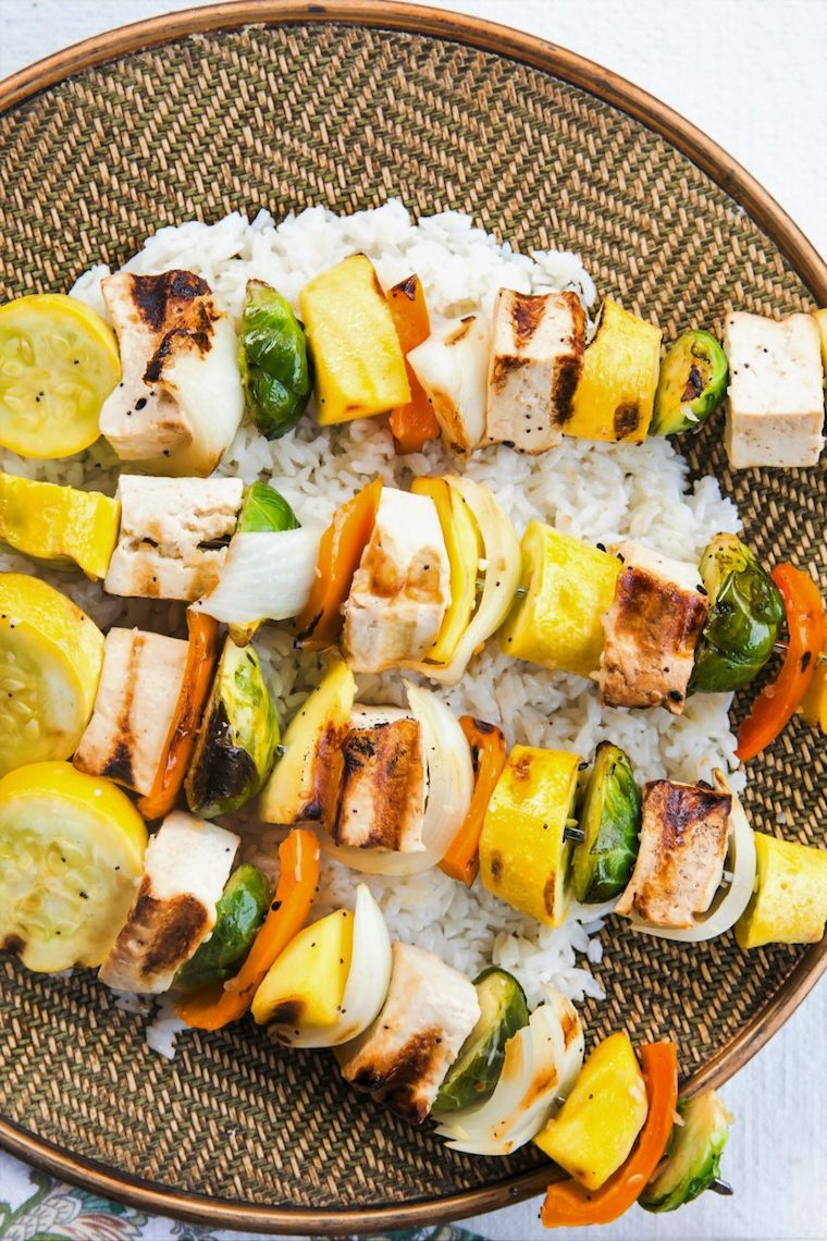 Birds eye view image of kabobs containing vegan sesame ginger tofu, zucchini, brussel sprouts, onions, and peppers, served on top of white, presented on a circular woven dish
