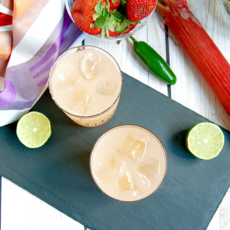Birds eye view shot of two spicy strawberry margaritas alongside fresh lime, jalapeno peppers, and whole strawberries on a dark surface