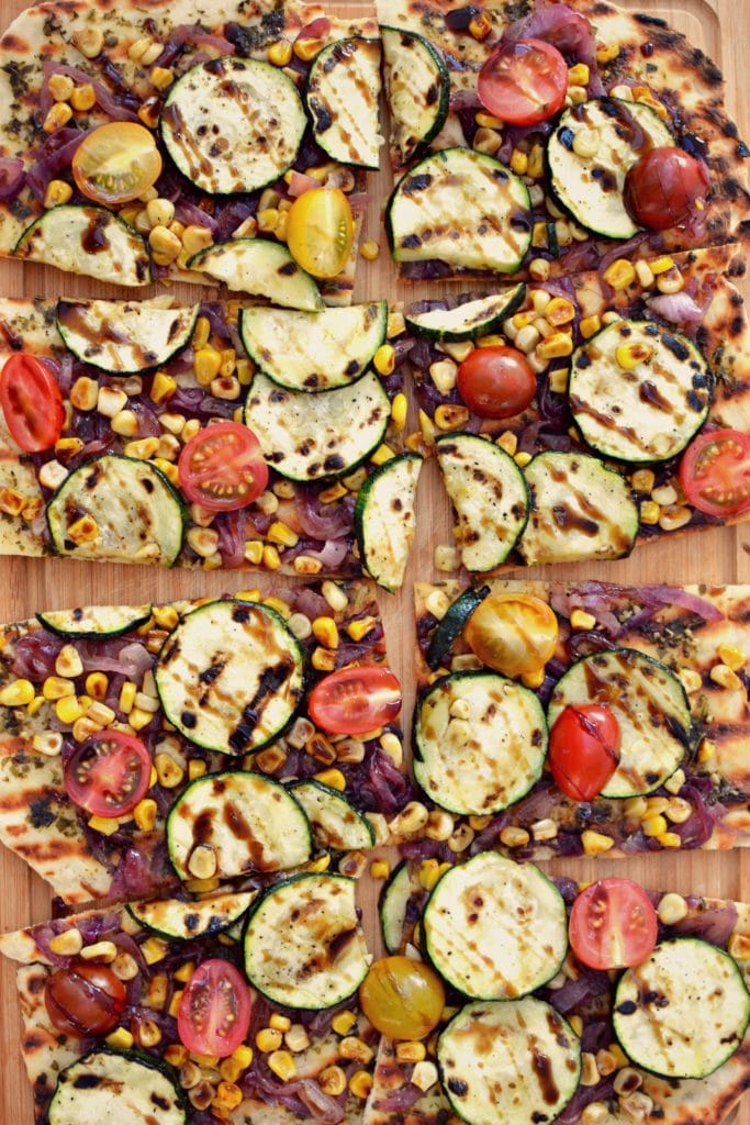 Birds eye view close up image of vegan veggie grilled square pizza slices containing pesto, zucchini, onions, tomatoes, and corn, garnished with balsamic, and served on a wooden platter
