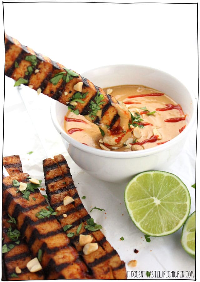 Close up image of a vegan grilled tofu skewer being dipped into a white bowl containing spicy peanut sauce alongside other tofu skewers, garnished with fresh lime, herbs, and chopped peanuts