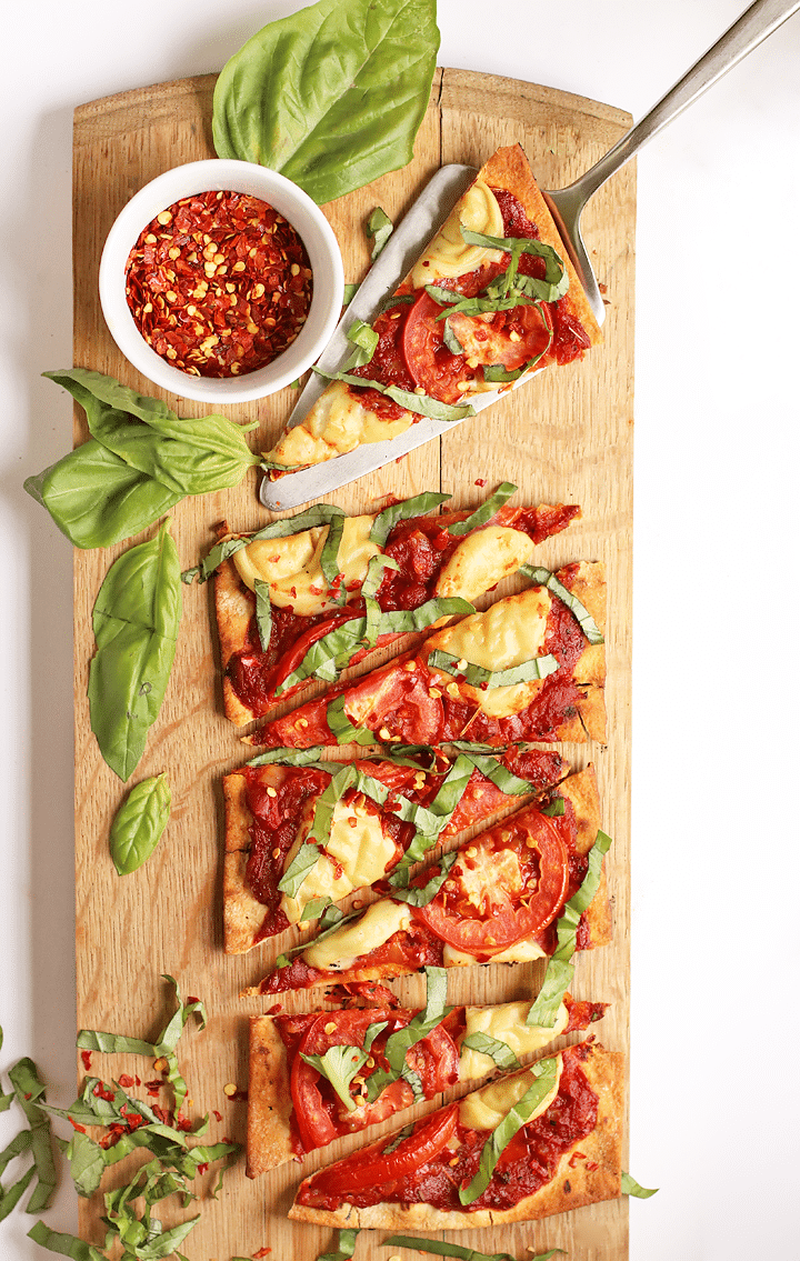 Birds eye view image of triangle slices of grilled vegan margherita pizza served on a rectangular wooden serving board, garnished with additional fresh basil and a small white ramekin of dried chilli flakes