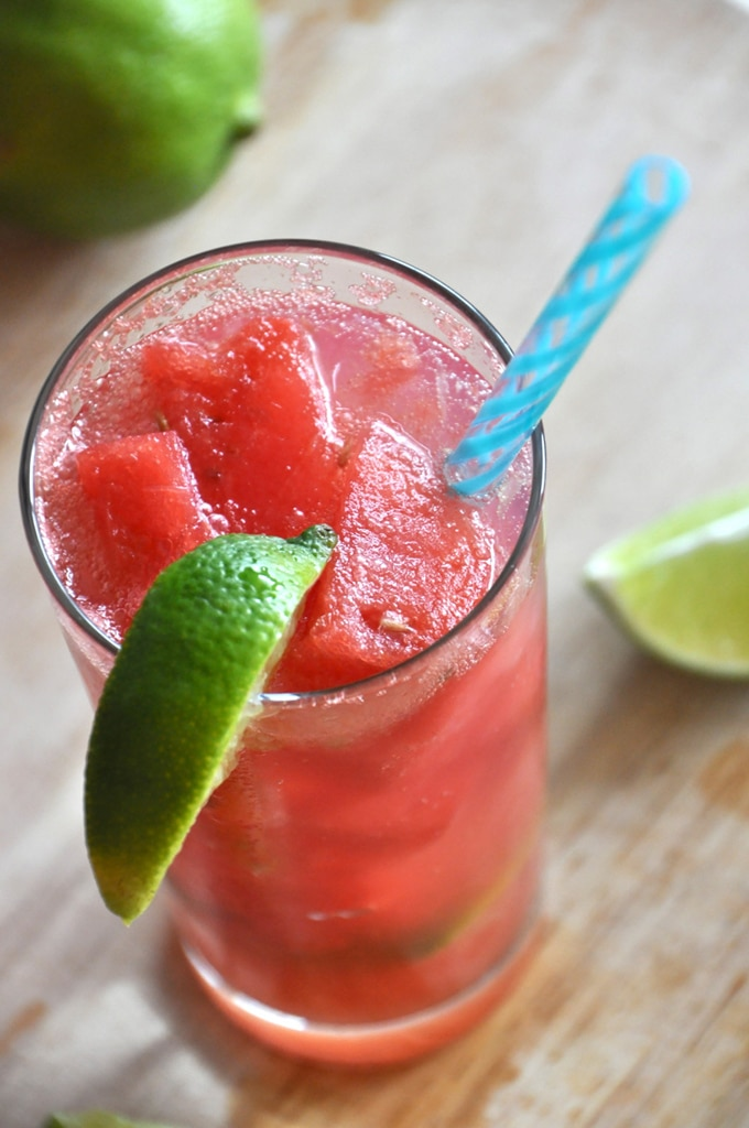 Close up of a vegan watermelon limemade cocktail presented in a large clear glass, served with a blue straw and a wedge of fresh lime