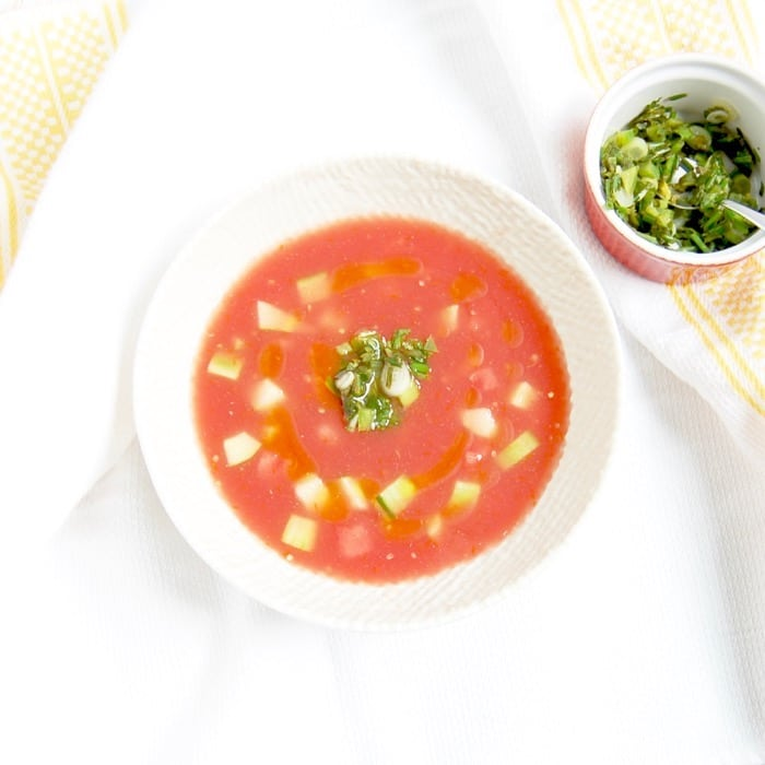 Birdseye view shot of vegan watermelon tomato gazpacho in a large white bowl garnished with scallion-cilantro relish, served next to a small red ramekin containing additional scallion-cilantro relish