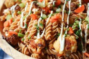 Buffalo cauliflower pasta salad in a wooden bowl.