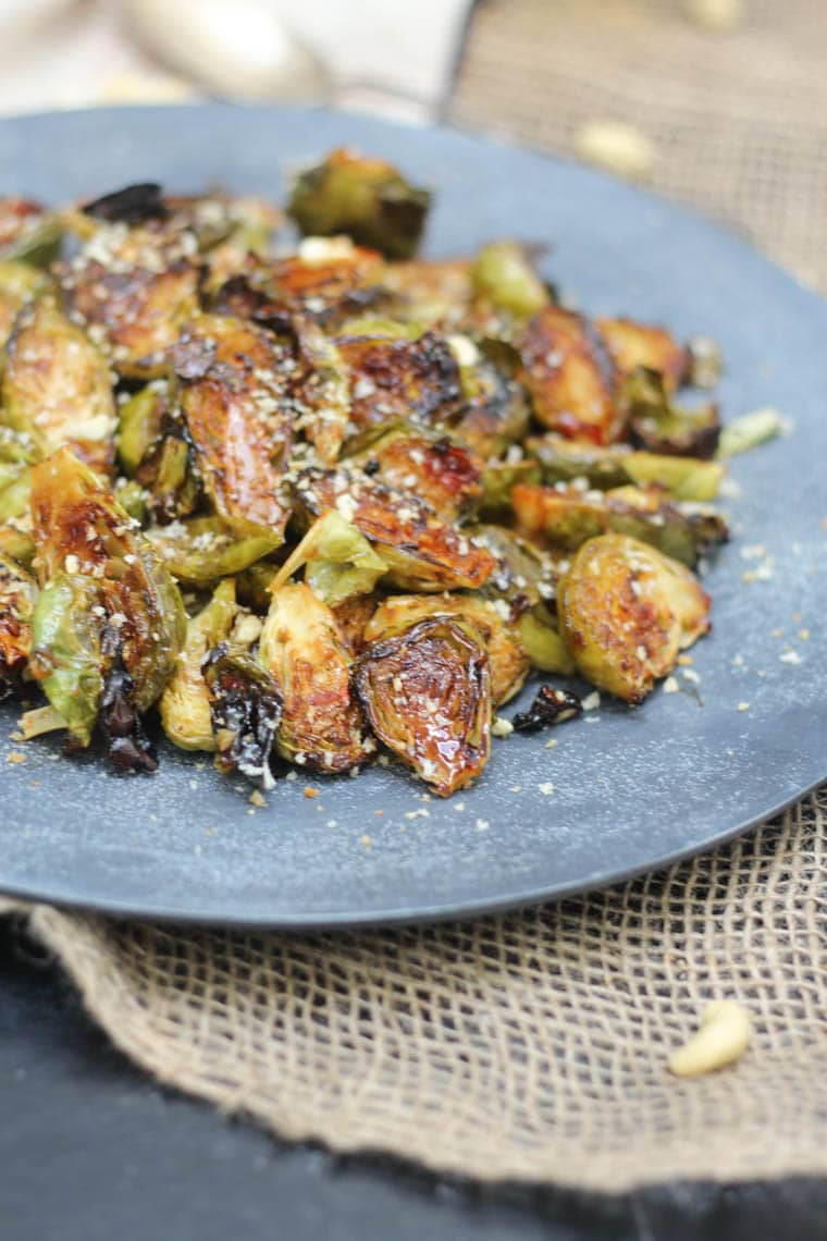 Close up of plant-based sweet-chilli roasted brussel sprouts garnished with a cashew topping served on a large blue dish