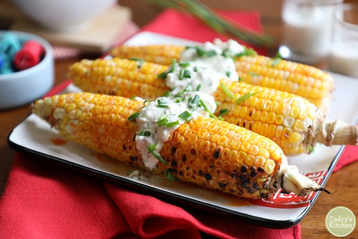 Close up image of three ears of corn on the cob garnished with vegan blue cheese dressing and chives, served on a square white serving dish with red detailing