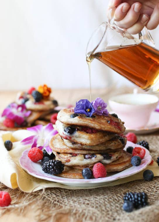 Stack of elderflower pancakes topped with edible flowers.