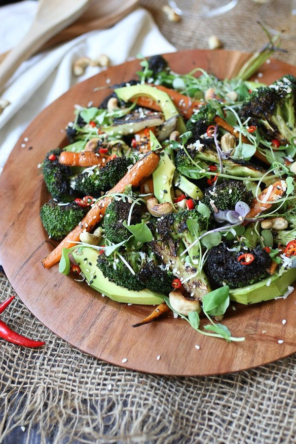 Grilled broccoli and carrot salad on a wooden plate.