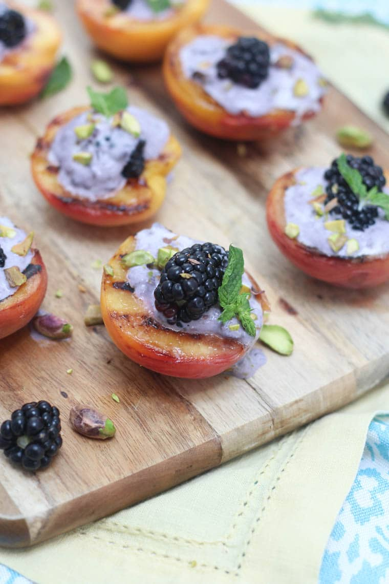 Close up image of several grilled peaches topped with blackberry coconut cream garnished with blackberries, pistachios, and mint, presented on a square wooden serving board