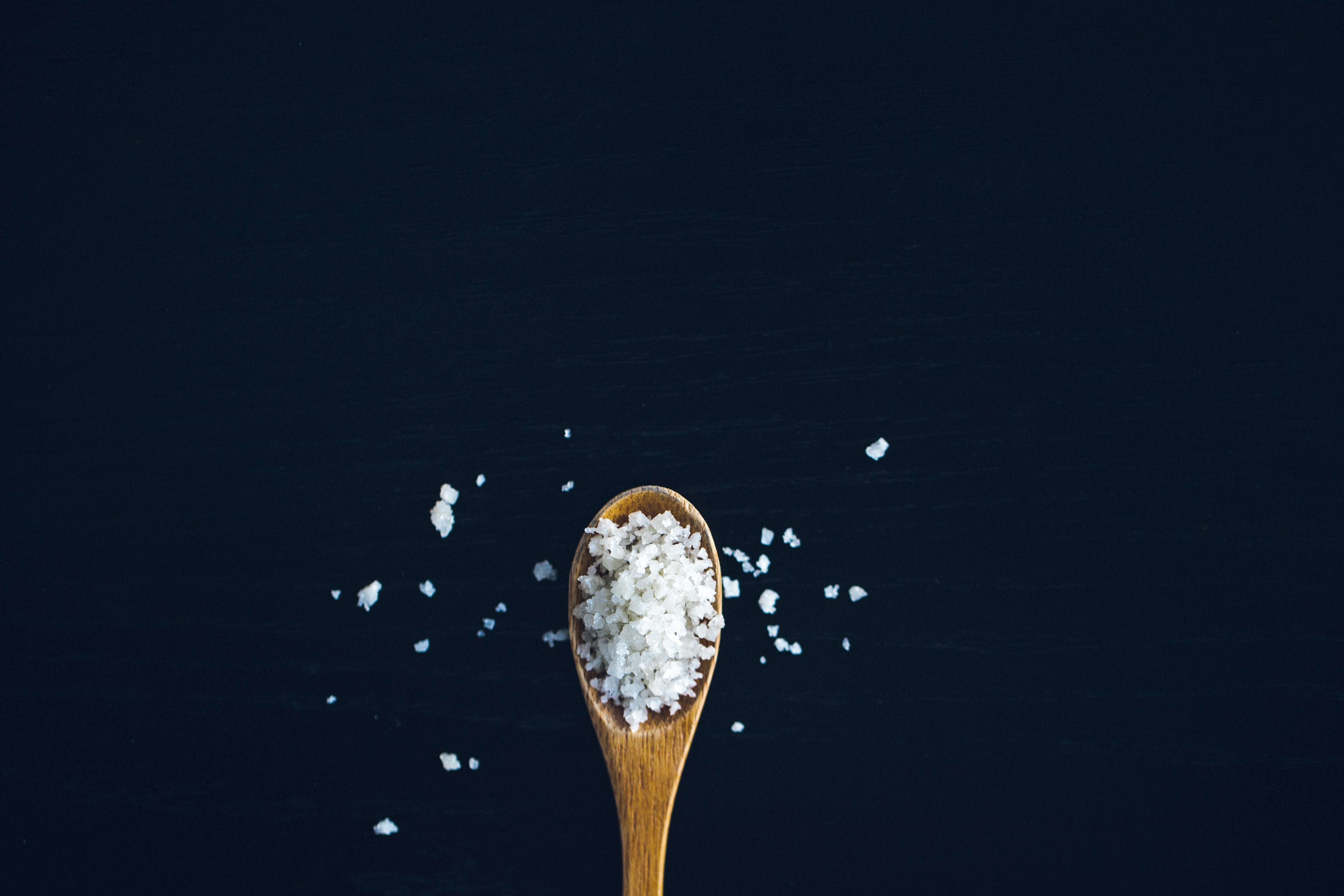 Coarse salt on small wooden spoon.