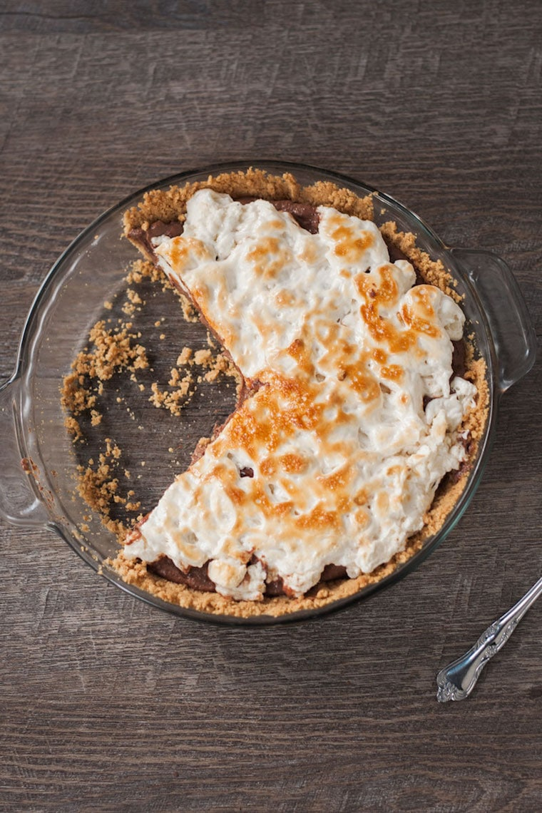 Birds eye view of plant-based s'mores pie with a slice cut out of it in a clear serving dish, garnished with additional graham cracker crumbs