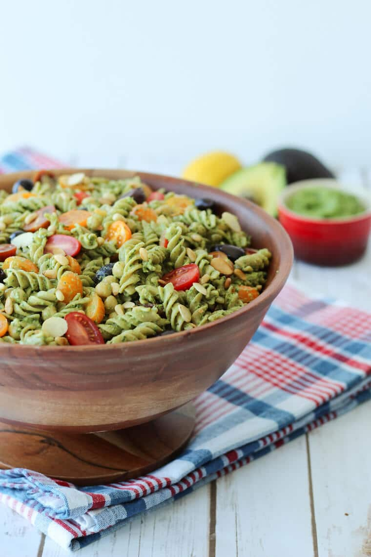 Close up of vegan pesto pasta salad with cherry tomatoes and olives garnished with additional roasted pine nuts served in a large wooden bowl on top of a plaid picnic blanket.