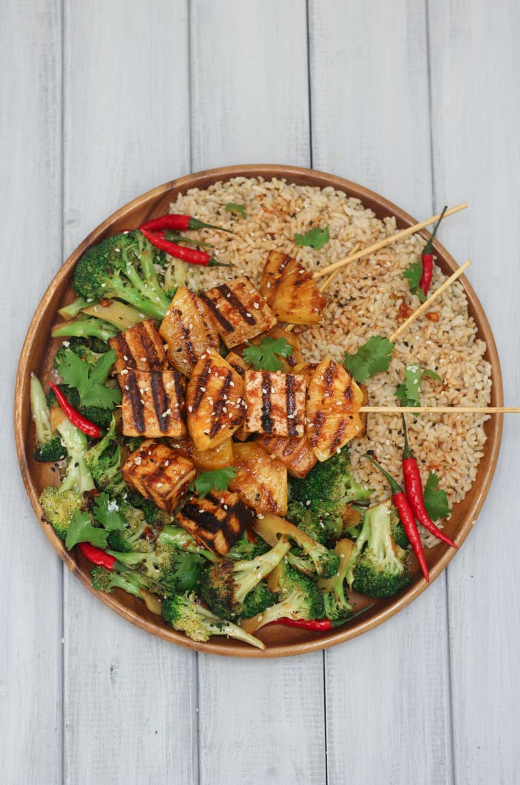Birds eye view image of vegan sriracha grilled tofu and pineapple chunks on wooden skewers, laying on top of green vegetables and brown rice, garnished with parsley and red chillis, served in a large circular bowl