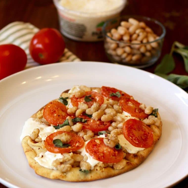 Tomato white bean naan pizza