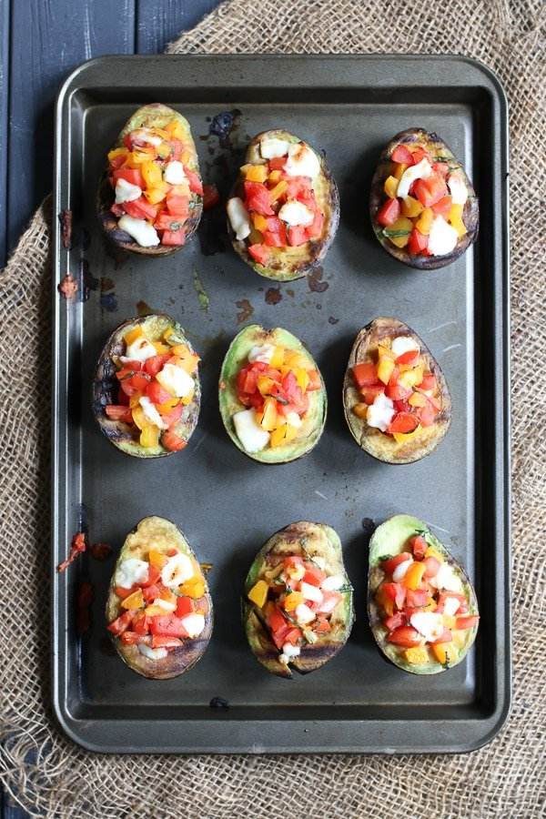 Grilled avocado bruschetta on a baking sheet.