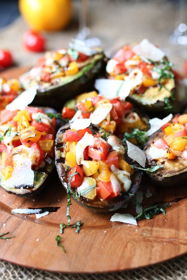 Grilled avocado bruschetta served on a wooden plate topped with parmesan and balsamic.