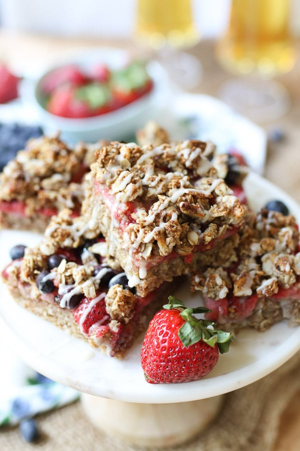 oat bars with berries stacked on a white plate with a strawberry on the side