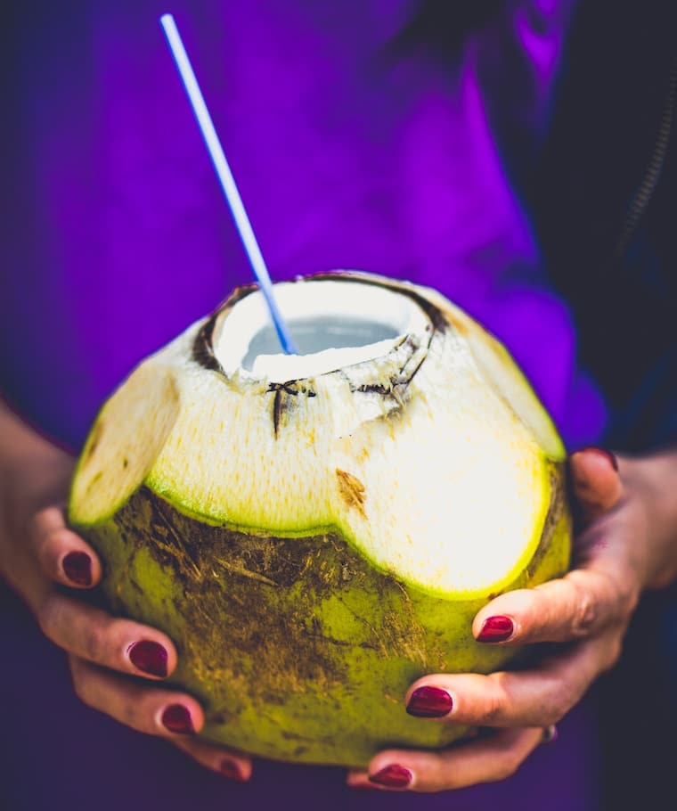Women holding a coconut with a straw sticking out.