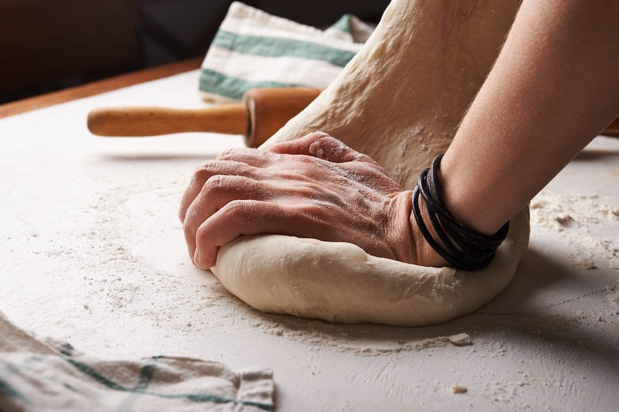 person kneading a ball of dough