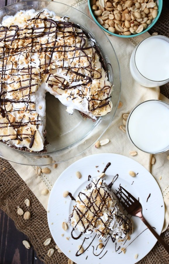birds eye view of frozen peanut butter pie next to a slice of no bake pie on a white plate garnished with chocolate and peanuts